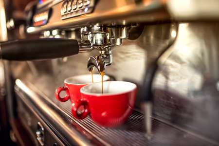 espresso machine: coffee machine preparing fresh coffee and pouring into red cups at restaurant, bar or pub. Stock Photo