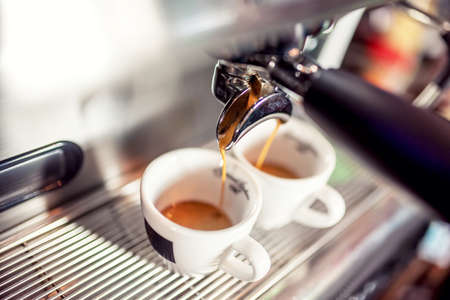 Espresso machine pouring fresh coffee into cups at restaurant. Coffee automatic machine making coffee