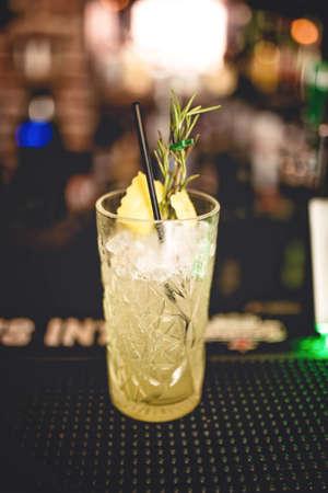 bebidas frias: sabor refrescante cóctel de bebidas alcohólicas en el bar local. Gin y Coctel de la cal con el romero y el hielo sirve frío por camarero