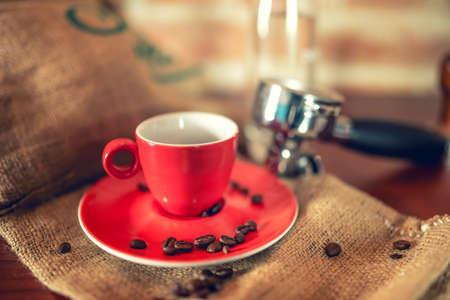 hot temper: taza de café con café espresso en pub con los estribos, los granos de café y el portafiltro. efecto de la vendimia en la foto