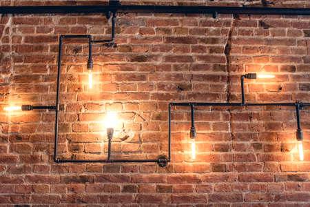 barra de bar: diseño de interiores de la pared de la vendimia. Diseño rústico, pared de ladrillo con bombillas y tubos, interior barra baja iluminada