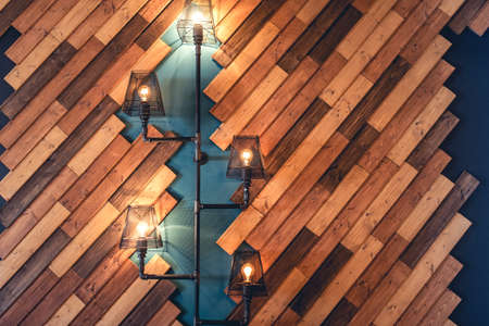 tendencies: Modern restaurant with rustic decorative elements. Interior design details with lamps and bulb lights. Wooden wall decoration with vintage looking lights Stock Photo