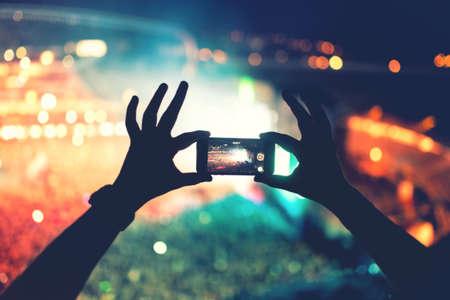 concerto rock: Silueta de las manos con la cámara del teléfono para tomar fotos y videos en el concierto de pop, festival. Efecto suave en foto