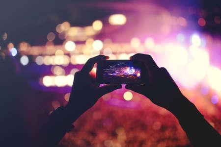 Silhouet van de handen opnemen van video's op muziek concert. Popmuziek concert met lichten, rook en veel mensen Stockfoto