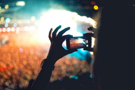 termine: Silhouette eines Mannes mit Smartphone, um ein Video in einem Konzert zu nehmen. Moderner Lifestyle mit hipster, die Fotos und Videos auf lokaler Konzert. Schwerpunkt auf der Kamera und Licht.