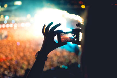 camera: Silhouette of a man using smartphone to take a video at a concert. Modern lifestyle with hipster taking pictures and videos at local concert. Main focus on camera and lights.