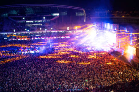 alzando la mano: Las personas felices que aplauden en concierto de la noche, la fiesta y que levantan las manos para el artista sobre el escenario. Vista aérea borroso de la muchedumbre del concierto