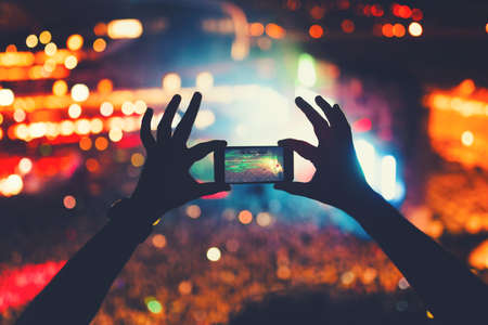 young hipster taking photos and videos at concert. Modern lifestyle with smartphone and parties.