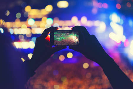 concert lights: Man holding phone and recording a concert, taking pictures and enjoying the music festival party