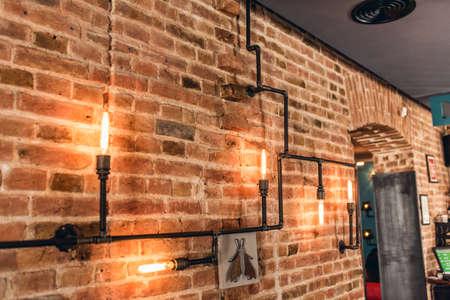 electricidad industrial: paredes del restaurante rústico, lámparas de diseño interior vintage, tubos de metal y bombillas Foto de archivo