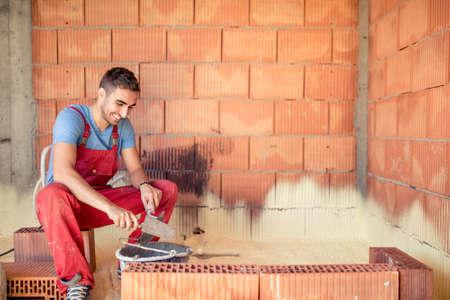 Construction mason worker, bricklayer building brick walls with spatula and mortar 免版税图像