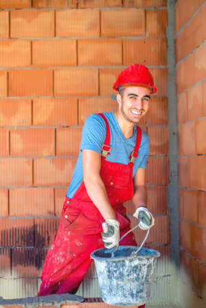 masonry: industrial builder working with mortar, bricks and tools on construction site Stock Photo