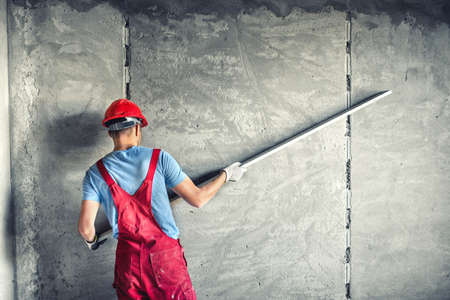 construction site helmet: industrial worker with plastering tools renovating a house. builder worker plastering facade industrial building with leveler