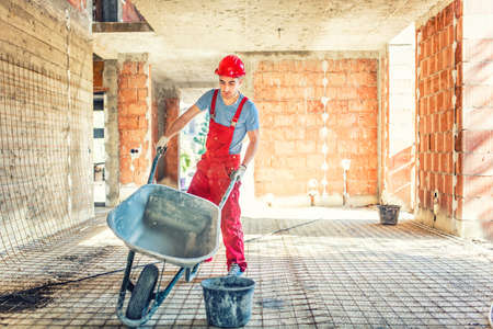 building material: worker with empty wheelbarrow on construction site