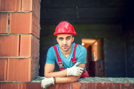 brick mason: portrait of industrial worker on construction site, sitting and relaxing after a hard day at work. Brick mason worker with protective gear