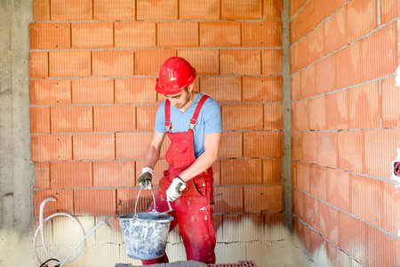 worker working: industrial construction worker, builder, working on construction site. Stock Photo