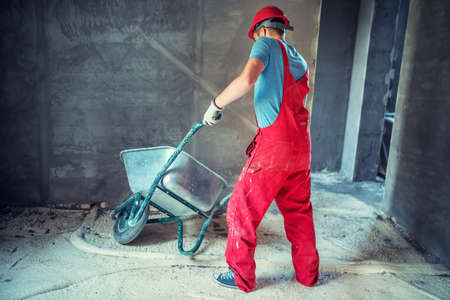 industrial worker, engineer on construction site, pushing a wheelbarrow