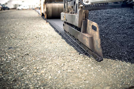 road works: industrial pavement truck laying fresh asphalt, bitumen during road works. Construction of highways and road works