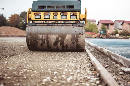 road paving: industrial compactor on construction site. Road paving and compacting during high way construction Stock Photo