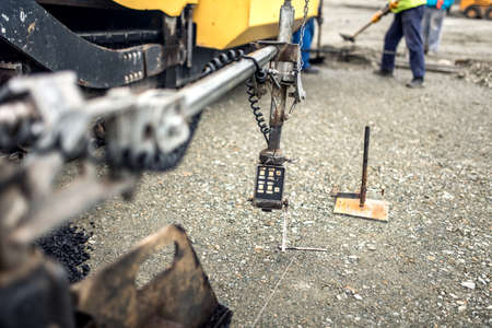 asphalting: guidance system of asphalting machinery, industrial asphalt layers Stock Photo