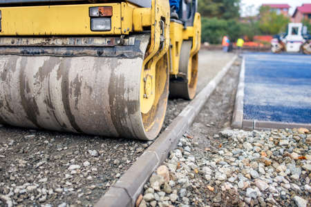 road paving: industrial compactor, road roller on construction site. Road paving and compacting during high way construction