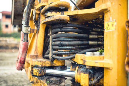 screw jack: hydraulic flexible pressure pipes and tubes. Close-up of industrial bulldozer with oil leaks