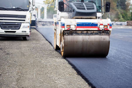 asphalting: Road works, asphalting and laying fresh bitumen during construction works. Industrial heavy duty compactor