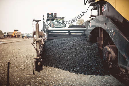 Paver machinery laying fresh asphalt or bitumen during road construction on building site. vintage, retro effect on photo