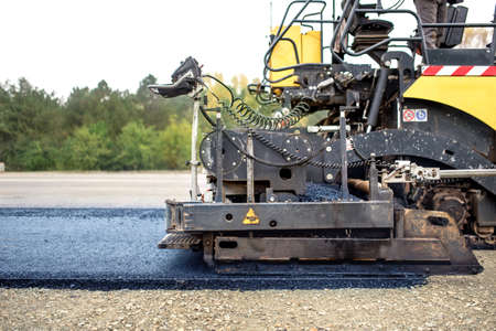 asphalting: industrial pavement truck laying fresh asphalt on construction site, asphalting