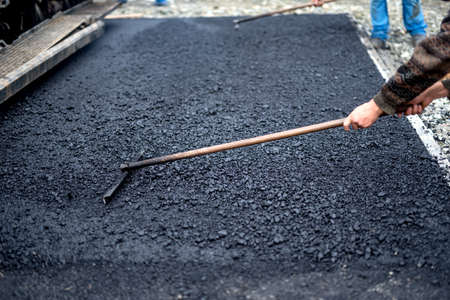 blacktopping: Worker leveling fresh asphalt on a road construction site, industrial buildings Stock Photo