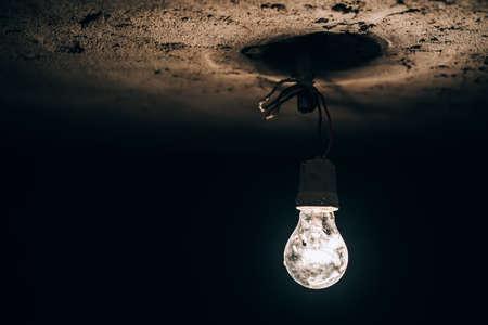 energia electrica: edad ronda bombilla que brilla intensamente en el sótano oscuro. improvisación de la electricidad en el sitio de construcción. Foto de archivo