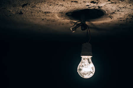 electric power: old round light bulb glowing in the dark basement. electricity improvisation at construction site. Stock Photo