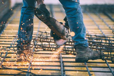 Industriële bouwtechnicus snijstaal met behulp van hoekmiter zaag, slijpmachine en gereedschap. Gefiltreerde afbeelding met retro effect Stockfoto