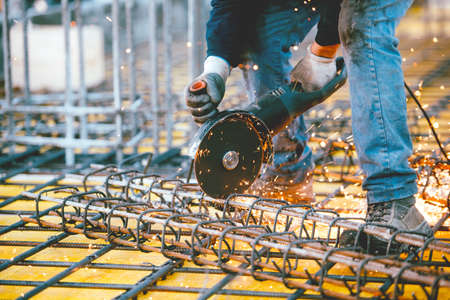 steel making: worker using an angle grinder for cutting steel, making sparks and debris Stock Photo