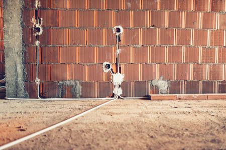 electric sockets installation in brick walls at house construction site 스톡 콘텐츠