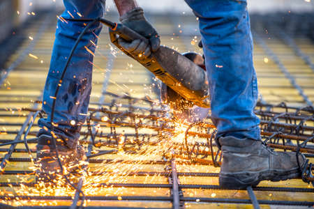 electrical materials: industrial worker cutting steel, sawing reinforced bars using angle grinder mitre saw Stock Photo