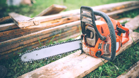 isolated man: close-up view of chainsaw, construction tools, agriculture details. Gardening equipment Stock Photo