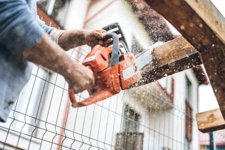 chainsaw: worker using an industrial chainsaw for cutting timber wood at construction site Stock Photo