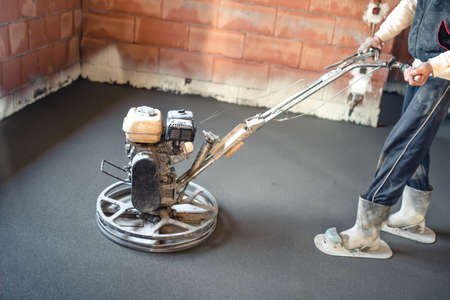 concrete surface finishing: Worker with power trowel tool finishing concrete floor, smooth concrete surface. Stock Photo