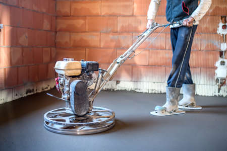 concrete surface finishing: Worker with power trowel tool finishing concrete floor, smooth concrete surface at house construction