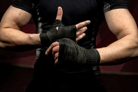 winner man: professional fighter preparing for training, wraping his hands and wrists