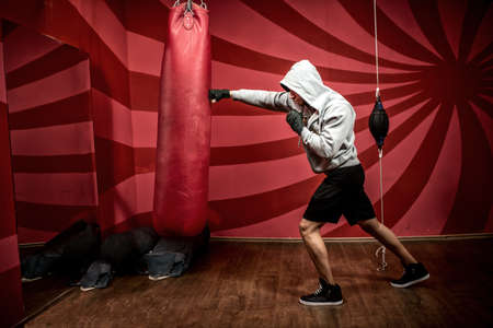 kickboxing: Athlete with hoody working out at boxing gym, getting ready for fight
