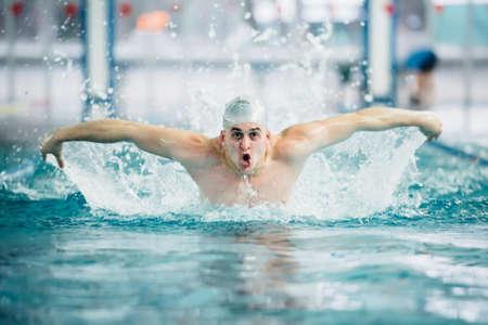 männlicher Schwimmer, die Schmetterlingsstil Technik bei Indoor-Pool durchgeführt wird. Vintage-Effekt