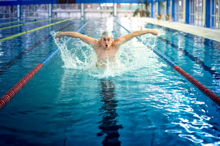 professional practice: Professional male swimmer, performing the butterfly stroke technique at indoor pool, swimming practice