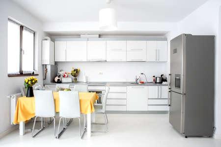Interior Design, moderne und minimalistische Küche mit Geräten und Tisch. Freiraum im Wohnzimmer, minimalistisches Dekor