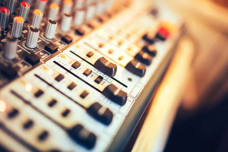 Close-up of music mixer button, setting volume. Music production mixer, adjustment tools