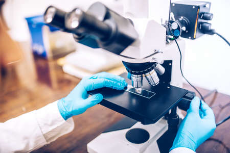 scientist hands using microscope for chemistry test samples and probes. medical and scientific detail equipment or tools