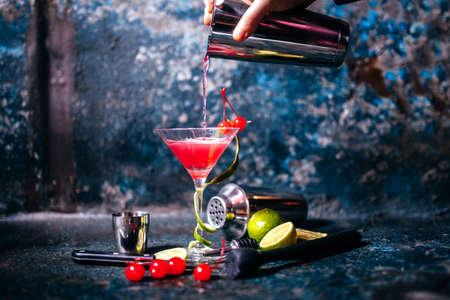 cocteles de frutas: barman, preparaci�n y verter c�ctel de color rojo en la clase de martini. Coctel cosmopolita en el fondo de metal
