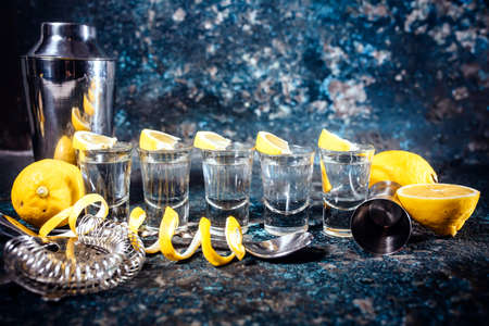 shooter drink: Silver tequila shots with lemon slices and cocktail elements. Alcoholic drinks in shot glasses served in pub or bar