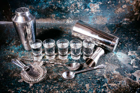 Bartending tools with cocktail shaker, shot glasses and alcoholic drinks. Bar details, nightlife glass alcoholic shots